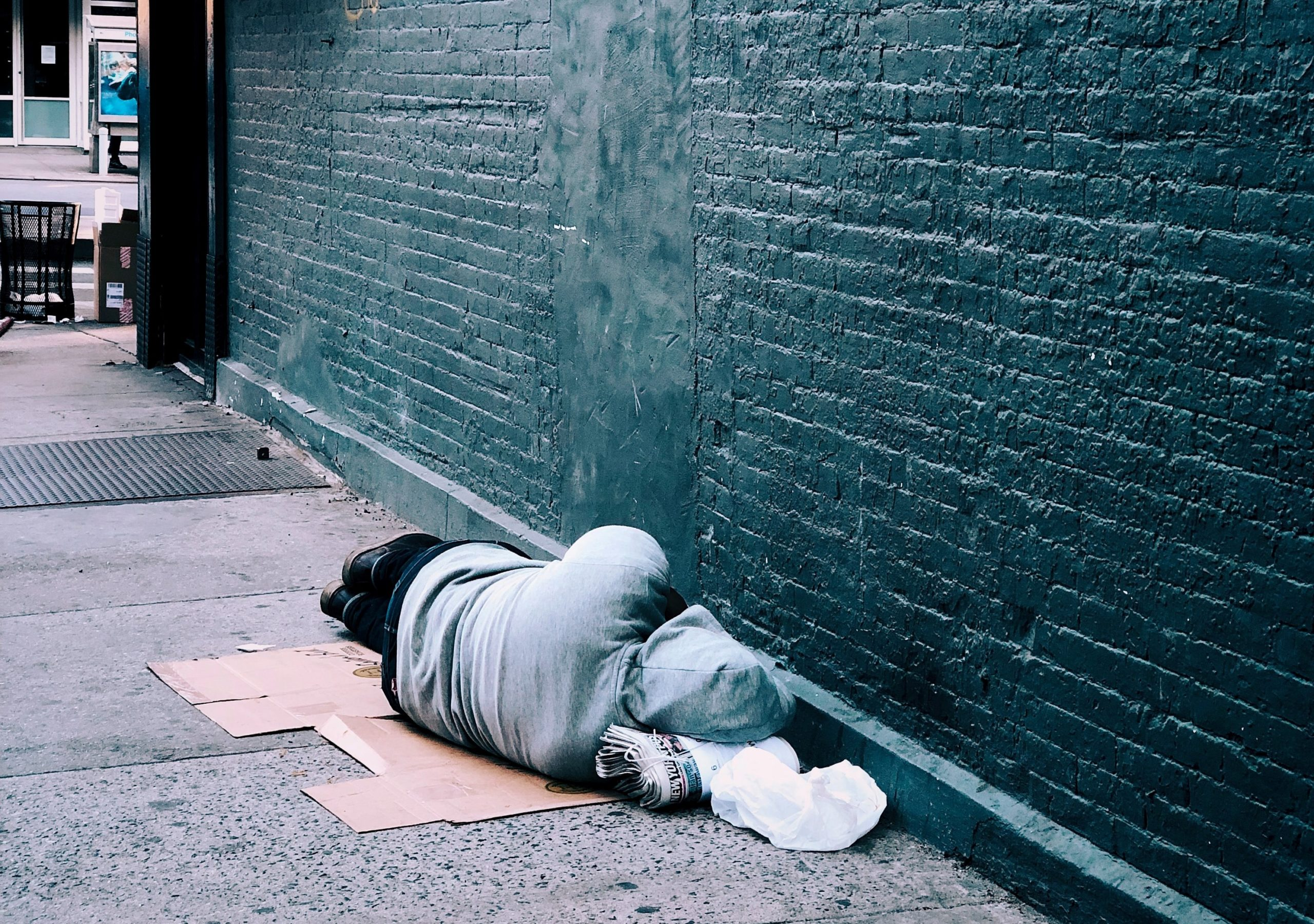 Man rough sleeping up against a wall on the street