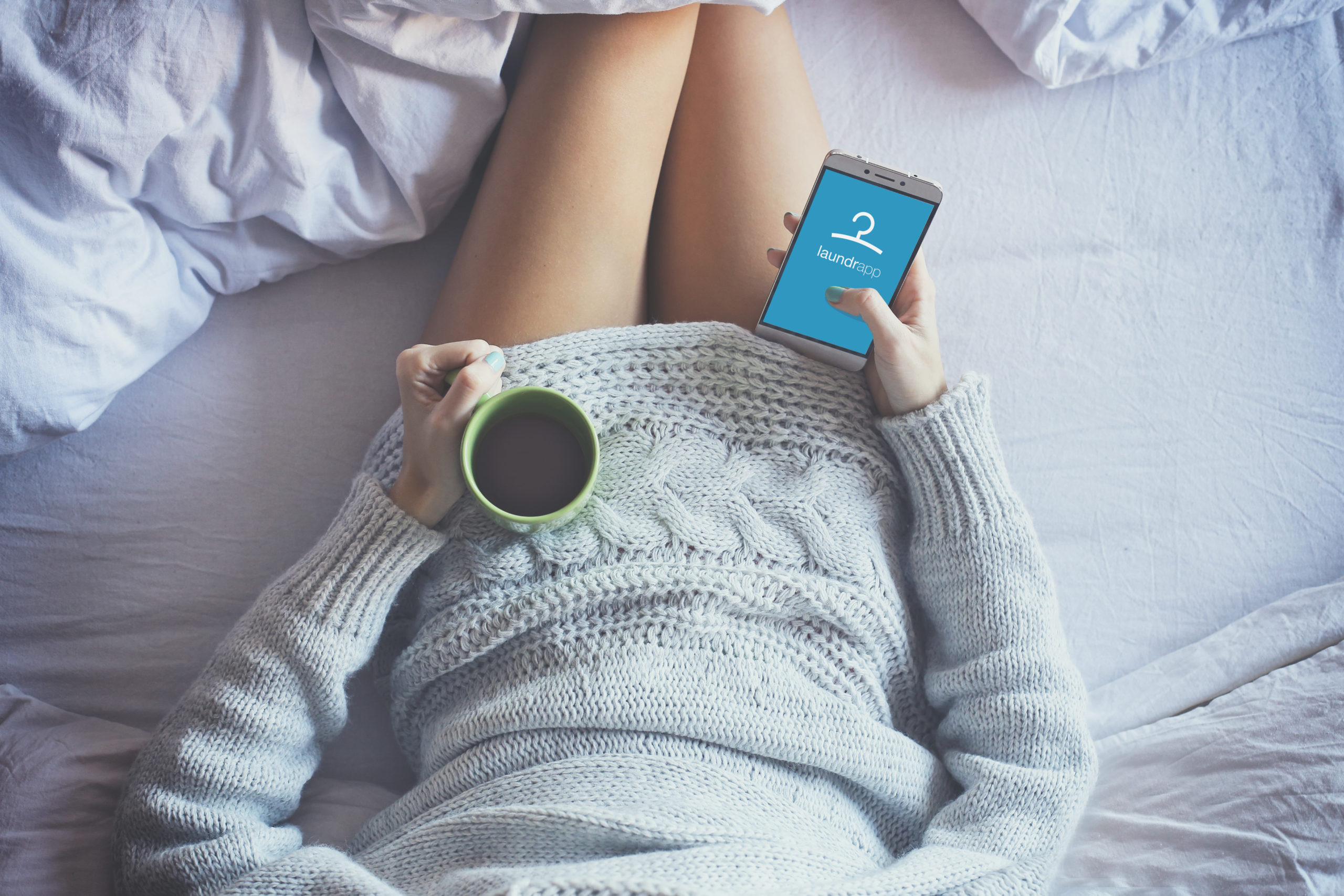 Woman in bed with coffee looking at Laundrapp on her phone