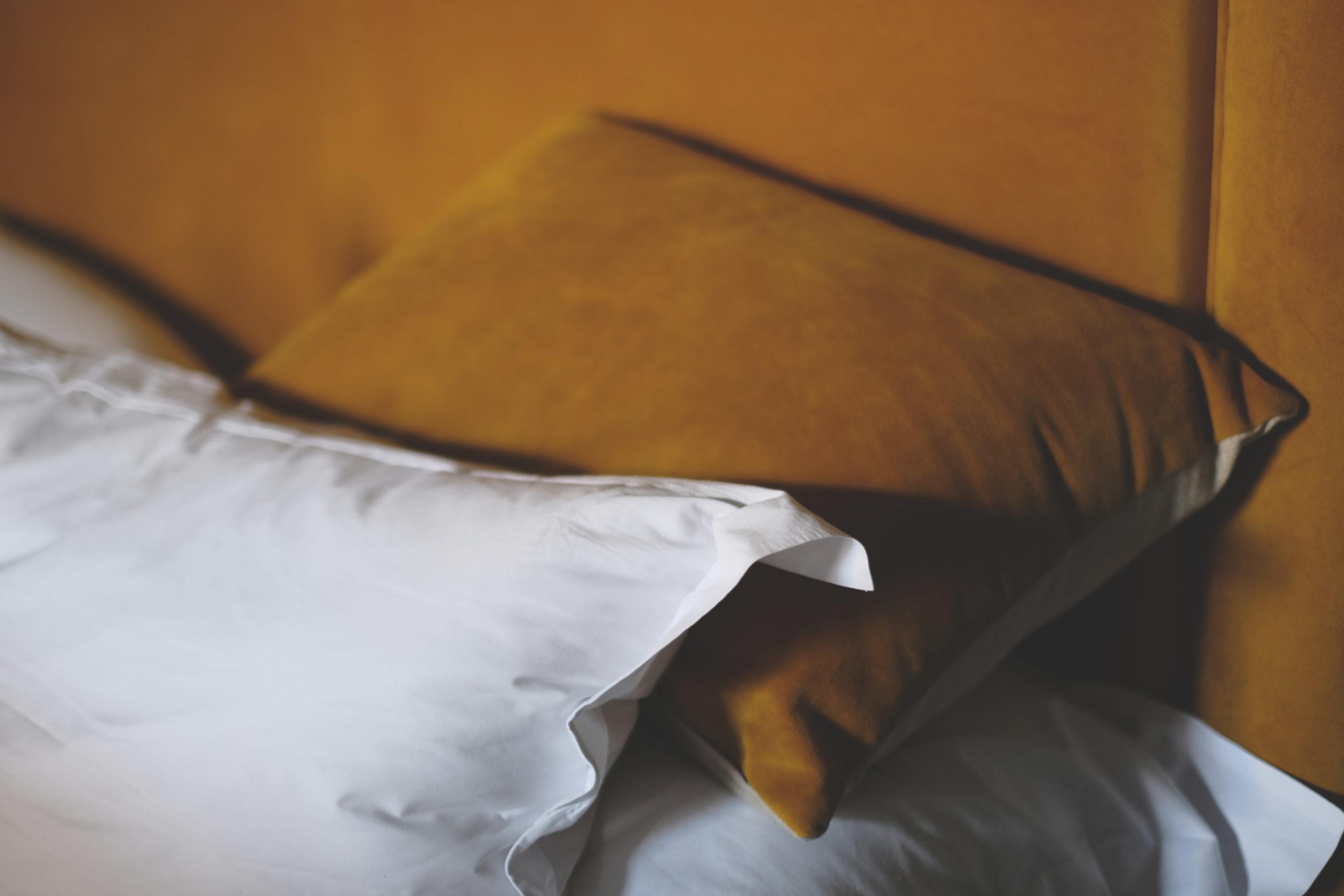 White pillow on top of a mustard brown velvet pillow.
