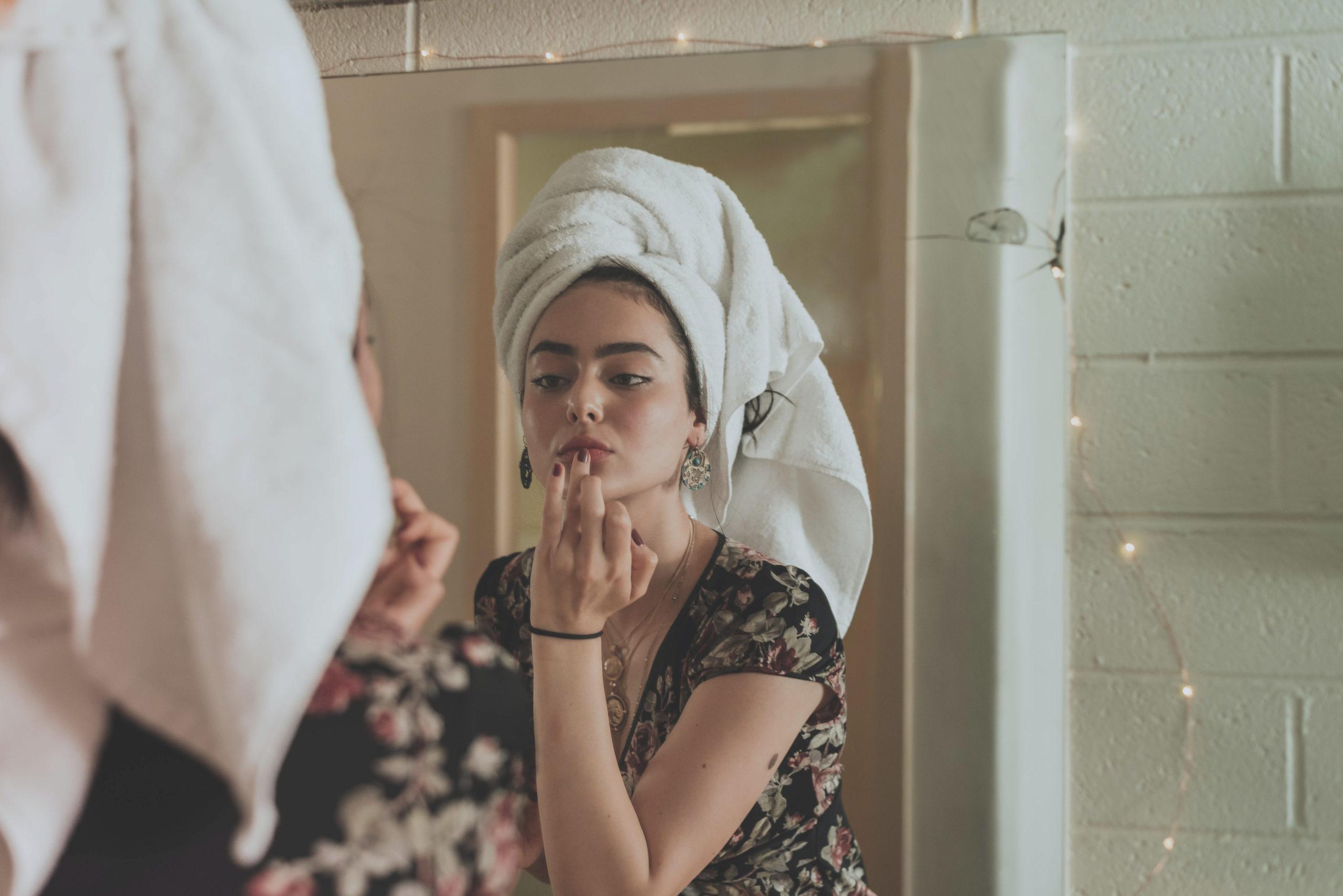 Woman with towel on head applying lip balm in the bathroom mirror