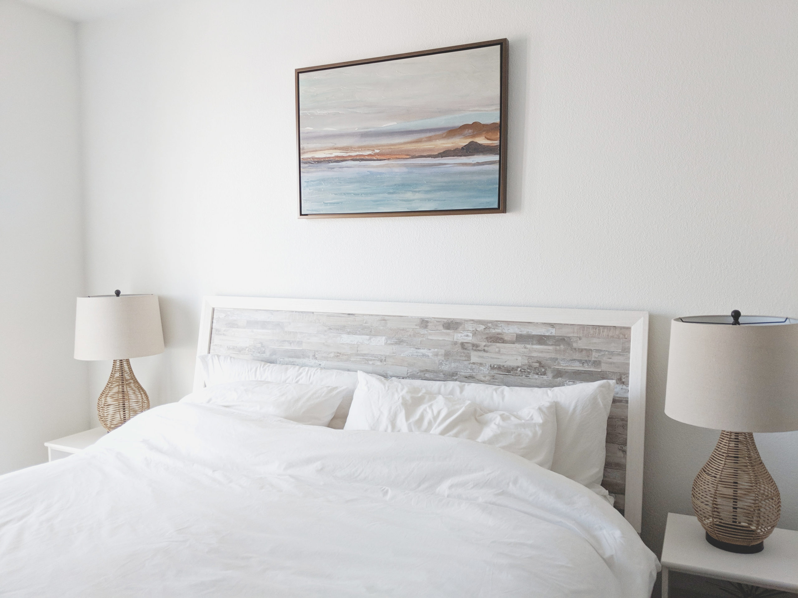 Bed with white bedding in between white bedside tables lamps