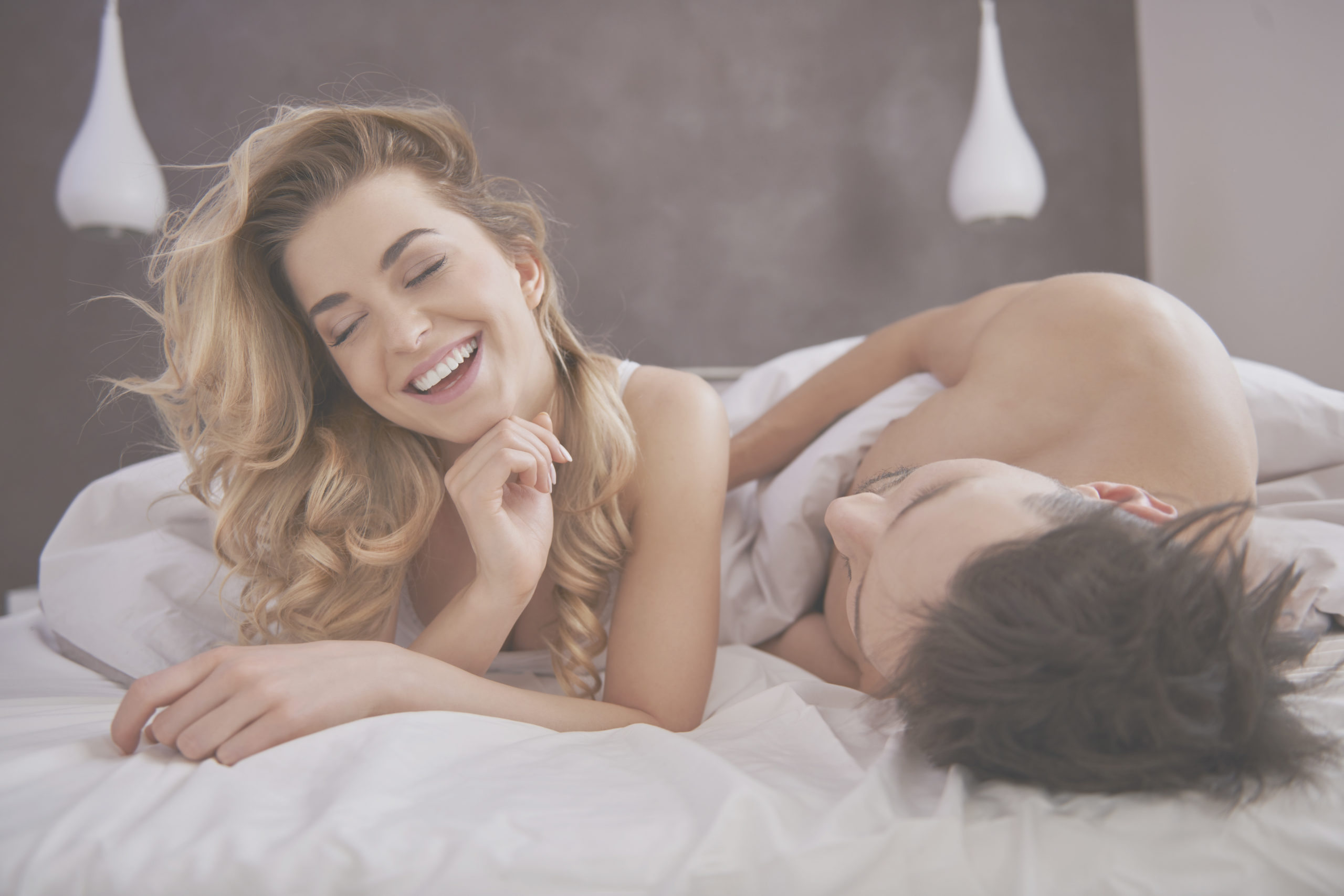 Woman smiling in bed next to man