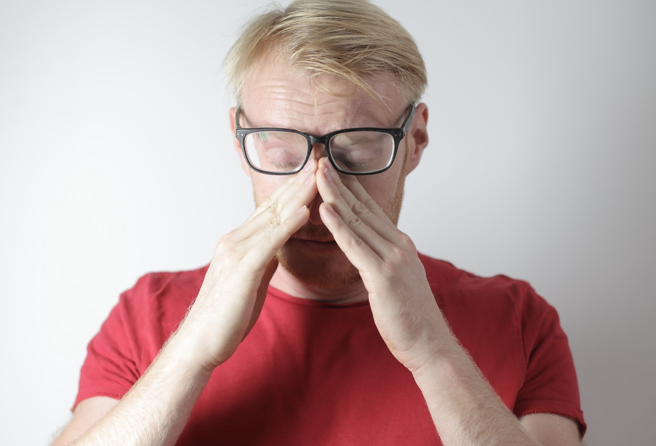 Man rubbing nose